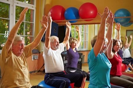 aerobic: Grupo Mixto haciendo ejercicios de espalda en un gimnasio