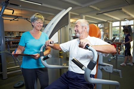 exercise machine: Fitness trainer explaining rowing machine in gym Stock Photo