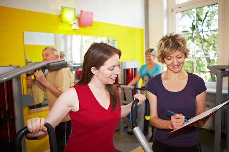 training device: Mixed group doing circuit training in a gym Stock Photo