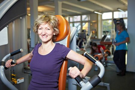 Happy woman exercising on rowing machine in gym photo