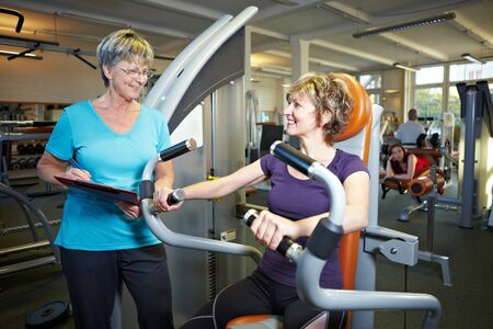 Fitness trainer explaining rowing machine to woman in gym photo