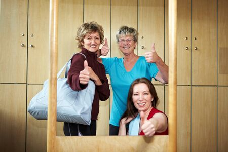 Three women holding their thumbs up in locker room photo