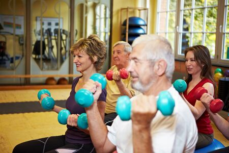 Mixed group doing dumbbell exercises in a gym photo