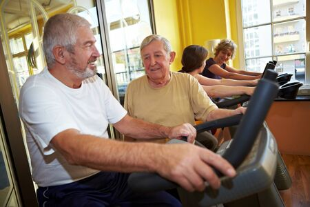 Two Seniors talking while spinning in a gym photo