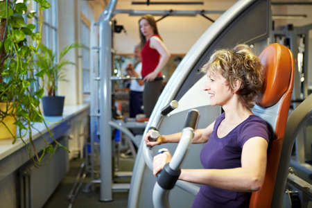 Happy woman working out on rowing machine in gym photo