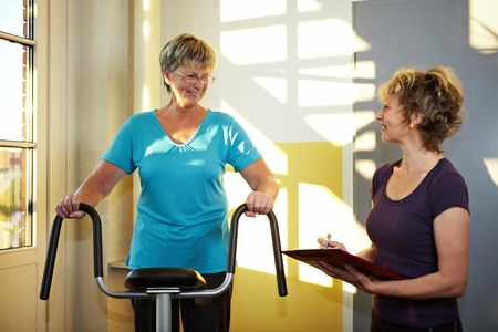 Trainer with eldery woman on treadmill in gym photo