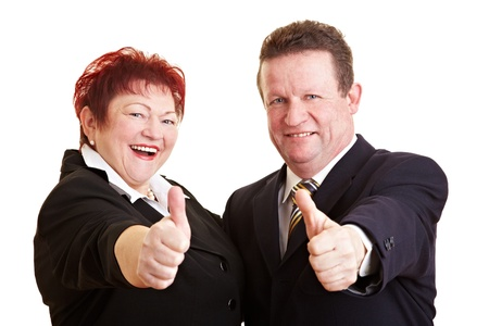 Two happy senior people in business suits holding their thumbs up photo