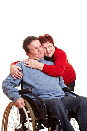 Elderly woman embracing her disabled man in wheelchair Stock Photo - 8597896