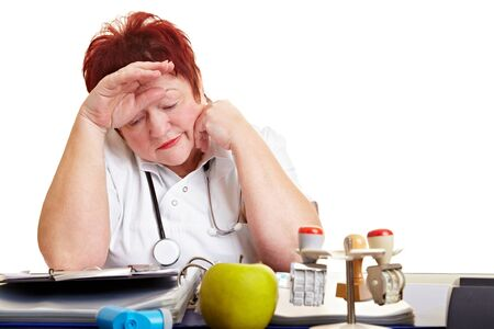 Tired female physician with burnout syndrome sitting at her desk Stock Photo - 8621253