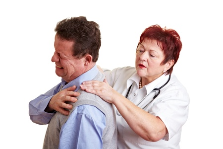 Female doctor examing back pain of a male patient photo