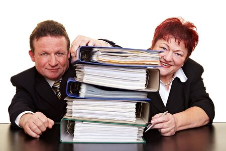 Two happy senior business people with a stack of files photo