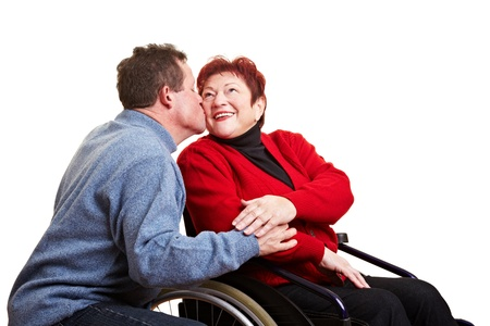 Senior man kissing his disabled wife in a wheelchair photo