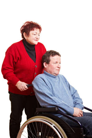 Elderly woman driving her disabled man in wheelchair photo