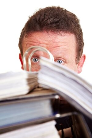 Surprised elderly business manager hiding behind files photo