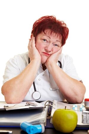 Sad female doctor with burnout syndrome sitting at her desk Stock Photo - 8621369