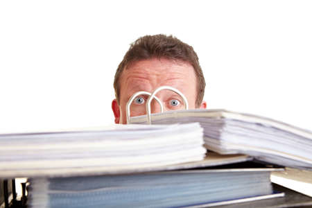 hideout: Business man afraid of tax audit hinding behind files Stock Photo
