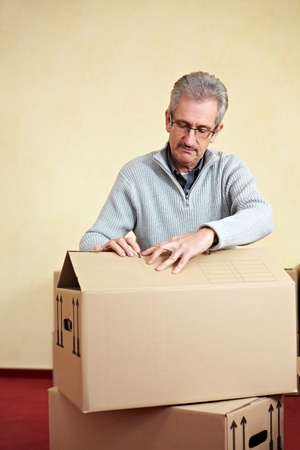 Elderly man opening the lid of a packing case while relocation house Stock Photo - 8903525