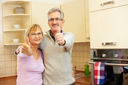 Two happy senior people in kitchen holding thumbs up photo