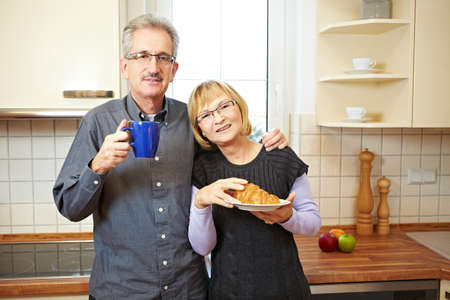 Happy senior couple having breakfast in the kitchen Stock Photo - 8903575