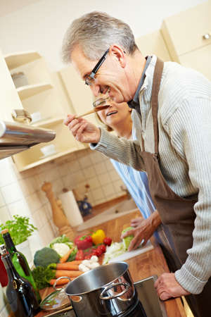 Two happy senior people cooking in the kitchen Stock Photo - 8903526