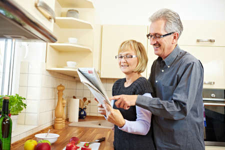 Senior couple reading classifieds in the newspaper in the kitchen Stock Photo - 8903529
