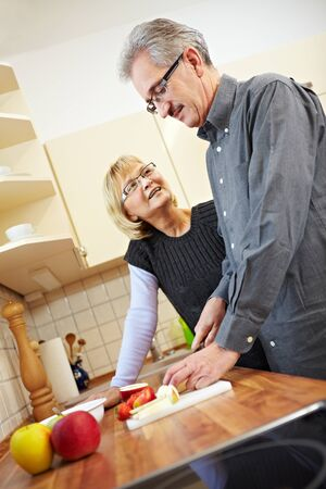 Husband preparing fruits for granola in the kitchen while wife is watching Stock Photo - 8903531