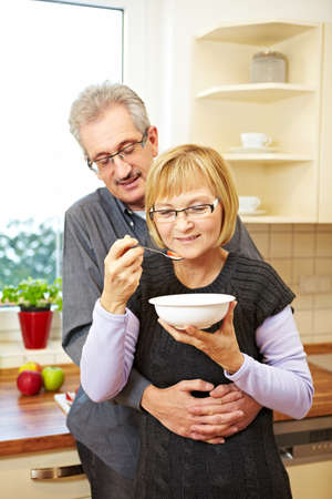 Elderly woman eating muesli in the kitchen while husband is embracing her photo