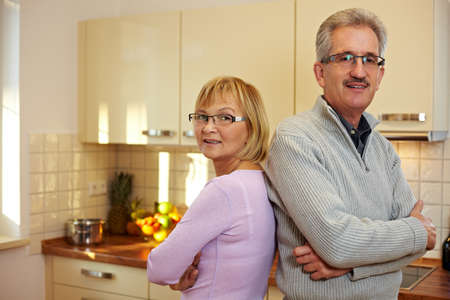 Happy senior couple with arms crossed in a kitchen Stock Photo - 8903587
