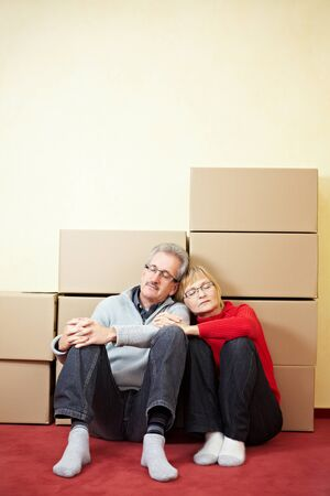 Senior couple sleeping in front of stacked moving boxes photo