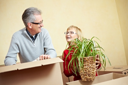 Senior woman packing spider plant in a moving box photo