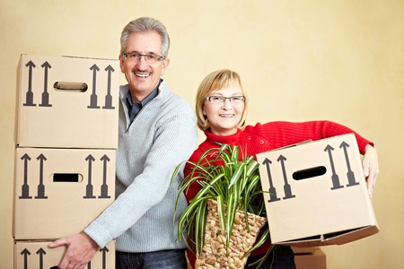 seniors homes: Two happy senior people with many moving boxes