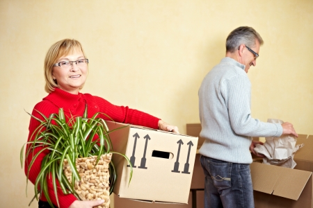 head home: Two happy senior people with many moving boxes