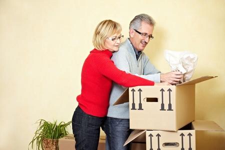 uitpakken: Twee senior mensen die spullen in een bewegende vak Zoeken Stockfoto
