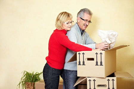 Two senior people searching stuff in a moving box photo