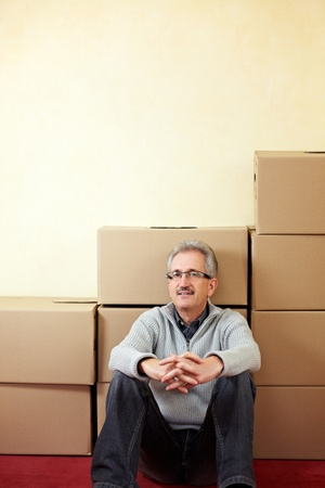Senior man sitting relaxed in front of moving boxes photo