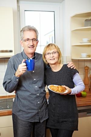 Happy senior couple having breakfast in the kitchen photo