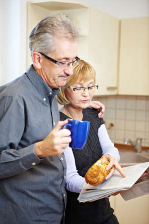Senior couple reading newspaper while eating breakfast in the kitchen photo
