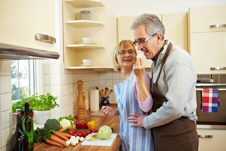 Woman cutting kohlrabi in the kitchen and man tasting it photo