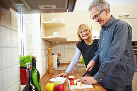 Husband preparing fruits for granola in the kitchen while wife is watching Stock Photo - 8903604