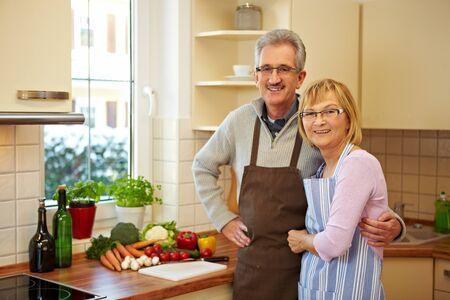 anciano feliz: Ancianos felices pareja permanente sonriendo en una cocina nueva Foto de archivo