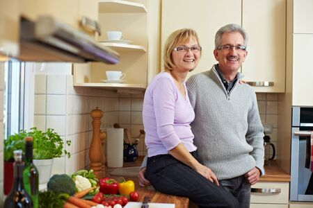 seniors homes: Happy elderly couple smiling in a new kitchen Stock Photo