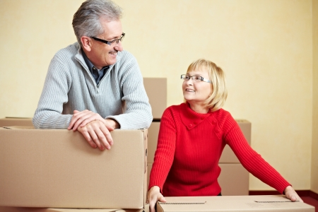 Two happy senior people with many moving boxes photo