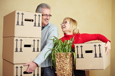 packing boxes: Two happy senior people with many moving boxes