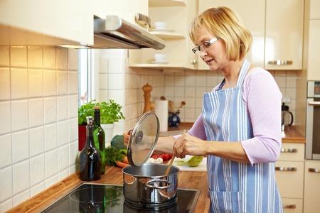 mujeres cocinando: Anciana en la cocina en una estufa cocinar sopa