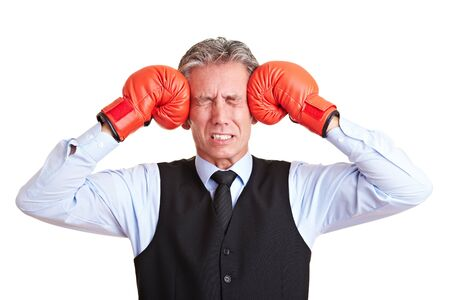 pangs: Senior manager pushing red boxing gloves against his aching head Stock Photo
