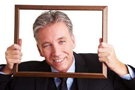 Lachende senior business man kijken door een leeg kader