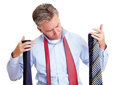 Elderly business man holding many different ties in his hands Stock Photo
