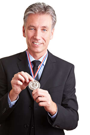 Proud elderly business man showing a silver medal around his neck photo