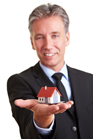 Elderly business man holding a small miniature house on his palm photo