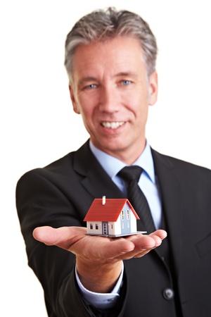 courtier: Homme d'affaires �g�s tenant une petite maison miniature sur sa paume